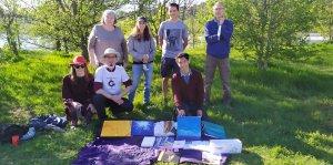 Sur de l'herbe, un drap sur lequel sont posés des articles a vendre en monnaie libre. Derrière, un groupe de 7 personnes.