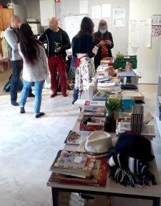 Au premier plan, une table remplie de marchandises à vendre : vetements, livres, jeux. Derrière, cinq personnes debout discutent.