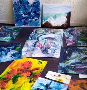Une dizaine de tableaux posés au sol. Motifs abstraits, évoquant le mouvement de l'eau, dans des tons bleus, sauf un tabluea dans les tons oranges.