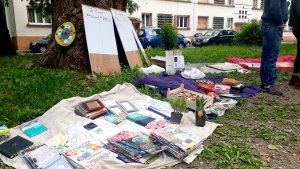 Sur de l'herbe, sur un drap posé au sol, des marchandises à vendre : livres, plantes, pain. En arrière-plan, des panneaux informatifs appuyés sur un arbre. Sur la droite, on voit les jambes de quelqu'un, debout.